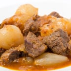 A bowl of traditional Greek stifado, a beef, onion and tomato st